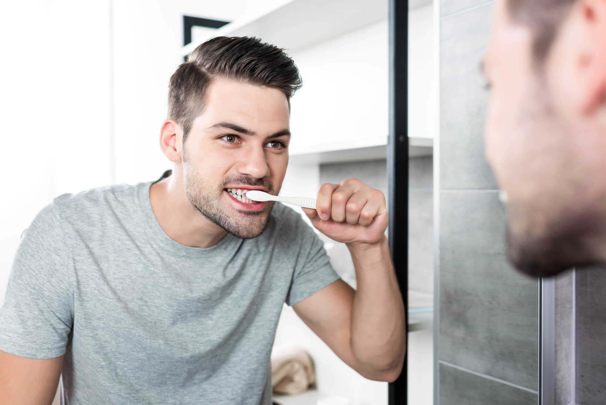 man brushing his teeth in front of the mirror as recommended by his Dentist North Charleston SC